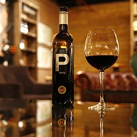 A bottle of 2015 Pares Balta Das Petit cabernet wine sits on a table near the retail wine section of The Pennsylvania Market