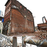 Condemned buildings are torn down next to the Garden Theater on the North Side.