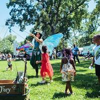 Children dance under Whimsy the Fairy's bubbles