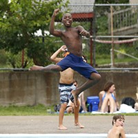 Jordan, 11, jumps into the Bloomfield pool while posing for the camera