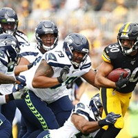 James Conner carries the ball while being followed by the Seattle defense.