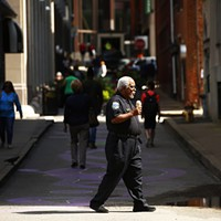 A security guard crosses Strawberry Way in Downtown Pittsburgh