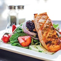 Salmon Salad: Norwegian salmon filet, red onions, cucumbers, pecans and seasonal fruits on a bed of spinach and arugula