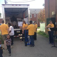 Striking PSO musicians unload a truck of food from 412 Food Rescue at Hawkins Village as two fellow members play soothing chamber music for residents.