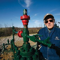 Ron Gulla stands at the site of one of four natural-gas wells on his property in Hickory, Pa. in 2009