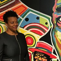 Janis Burley Wilson stands before a mural by Tarish Pipkins at the August Wilson Center.