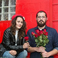 Pittsburgh Democratic Socialists of America co-chairs Arielle Cohen and Adam Shuck holding red roses, the symbols of democratic socialism