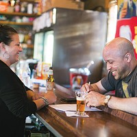 DeeDee, a bartender at Howard's for 15 years, shares a laugh with a customer