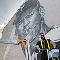 Jeremy Raymer in front of his Roberto Clemente mural