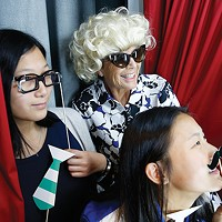 Guests wear props inside the photobooth at The Andy Warhol Museum.