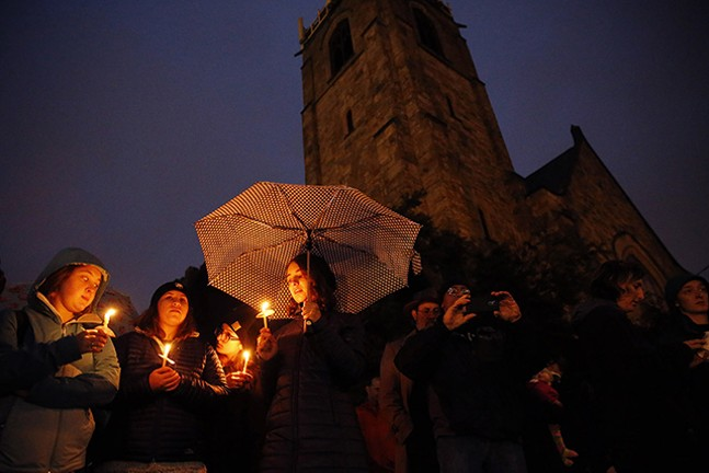 People lit candles while attending an interfaith vigil at Sixth Presbyterian Church in Squirrel Hill. - CP PHOTO: JARED WICKERHAM