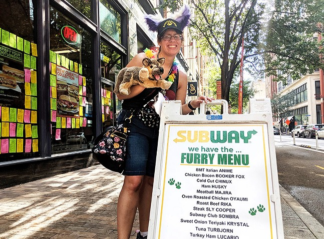 """Shortcake"" from Bethel Park poses with the Penn Avenue Subway ""furry menu."""
