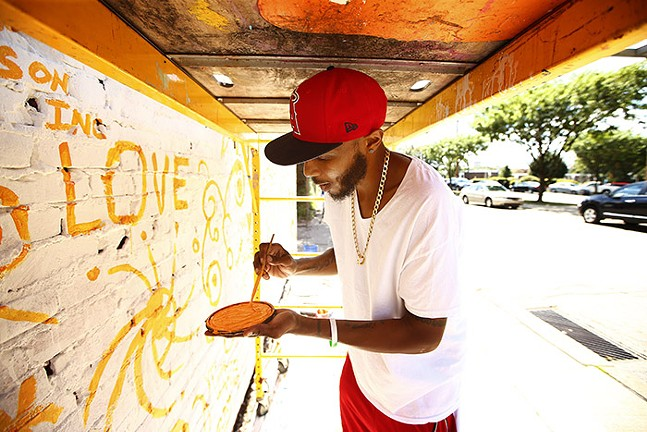Warren Jackson, president of New Vision Ministries, helps paint. - CP PHOTO: JARED WICKERHAM