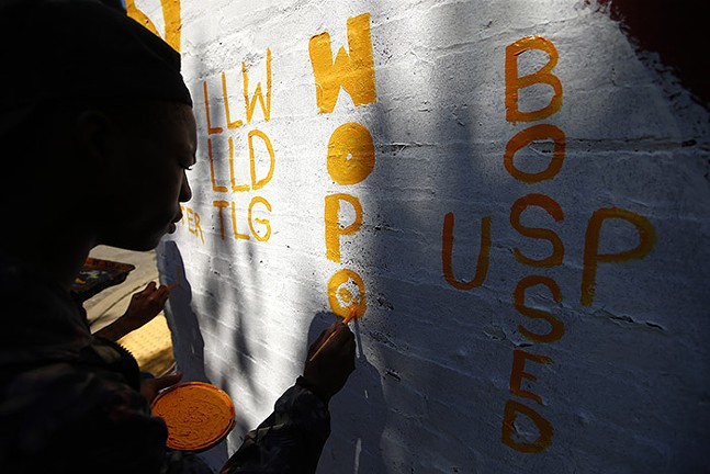 """East Liberty resident Jhamire Barnett helps paint the Mac Miller mural, started by Kyle Holbrook, by adding """"Wopo"""" in honor of Jimmy Wopo, a Pittsburgh rapper who was killed in 2018. - CP PHOTO: JARED WICKERHAM"""