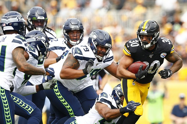 James Conner carries the ball while being followed by the Seattle defense. - CP PHOTO: JARED WICKERHAM