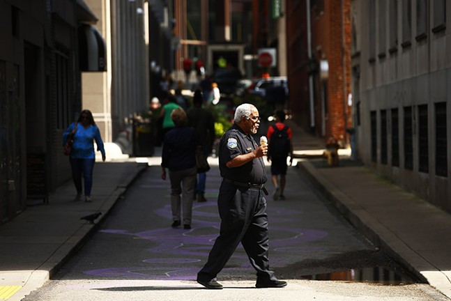 A security guard crosses Strawberry Way in Downtown Pittsburgh - CP PHOTO: JARED WICKERHAM