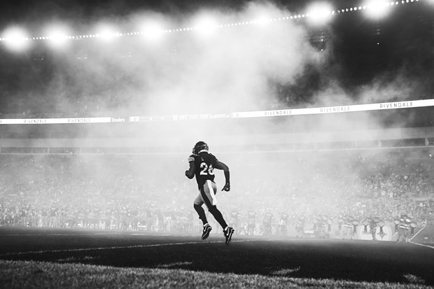 Mark Barron takes the field amidst smoke. - CP PHOTO: JARED WICKERHAM