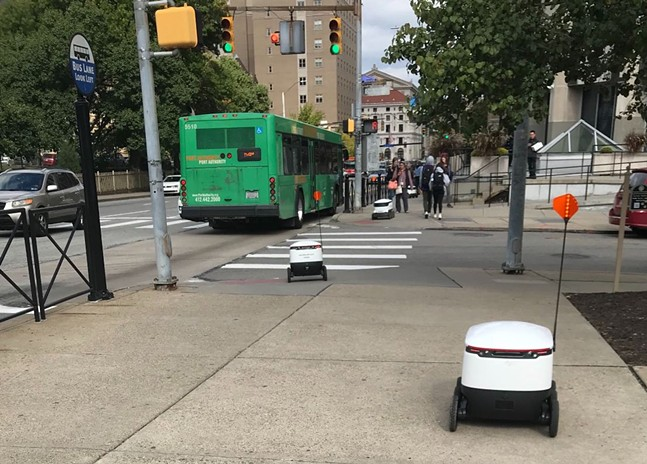 A line of Starship delivery robots on Fifth Avenue sidewalk in Oakland - CP PHOTO: ELISE LAVALLEE