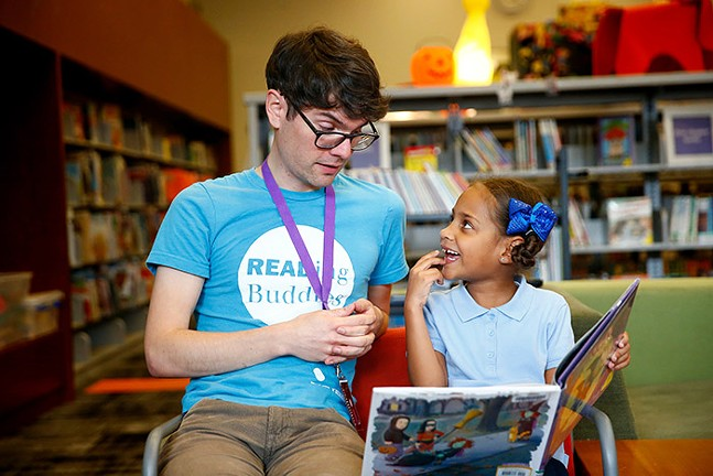 Daniel Hatfield, a volunteer with the Reading Buddy program, reads with Tyleah Williams, 7, at the North Side's Carnegie Library of Pittsburgh. - CP PHOTO: JARED WICKERHAM