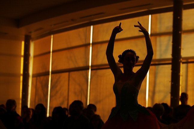 A dancer is silhouetted by the sunset during the Poinsettias and Pointe Shoes show. - CP PHOTO: JARED WICKERHAM