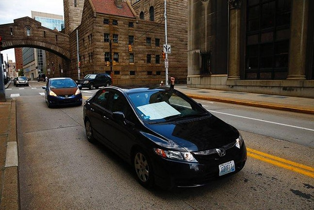 A car-only rally drives past the Allegheny County Jail in Downtown Pittsburgh. - CP PHOTO: JARED WICKERHAM