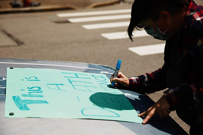 A protester pens a sign to hold during a car-only rally past the Allegheny County Jail in Downtown Pittsburgh. - CP PHOTO: JARED WICKERHAM