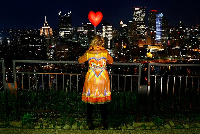 """Jena-Anne Sabon, an organizer of #LoveFromPGH, stands atop Mt. Washington with a lighted heart and a decorated jacket during """"Illumination-Ovation"""" on Tue., April 7. - CP PHOTO: JARED WICKERHAM"""