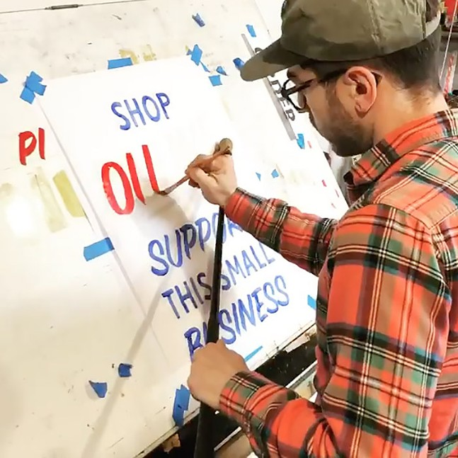 Daniel Gurwin painting one of his small business signs - PHOTO: INSTAGRAM.COM/DANIELGURWIN