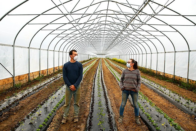 Chris Brittenburg and Aeros Lillstrom, owners of Who Cooks For You Farm, inside their greenhouse. - CP PHOTO: JARED WICKERHAM