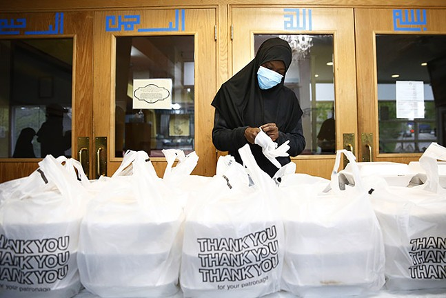 A volunteer puts on gloves before handing out Iftar boxes at the Islamic Center of Pittsburgh during Ramadan on Sun., May 3, 2020. - CP PHOTO: JARED WICKERHAM