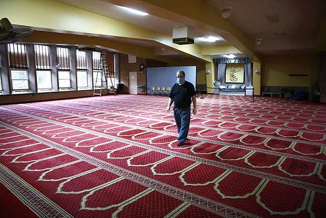 A volunteer walks through the large empty prayer room during Ramadan at the Islamic Center of Pittsburgh on Sun., May 3, 2020. - CP PHOTO: JARED WICKERHAM