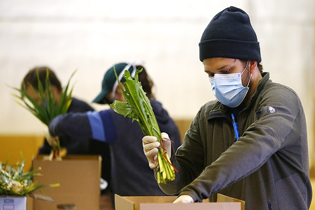 Derek Dumont puts together farm-share boxes at Harvie Farms Pittsburgh. - CP PHOTO: JARED WICKERHAM