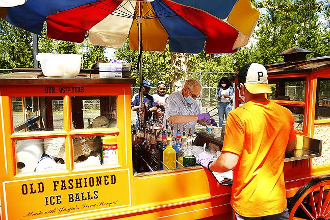 Gus Kalaris, owner of Gus & Yiayia's food cart, serves up old-fashioned shaved ice balls with employee Matt Szymanowski in the North Side on Thu., May 21, 2020. - CP PHOTO: JARED WICKERHAM