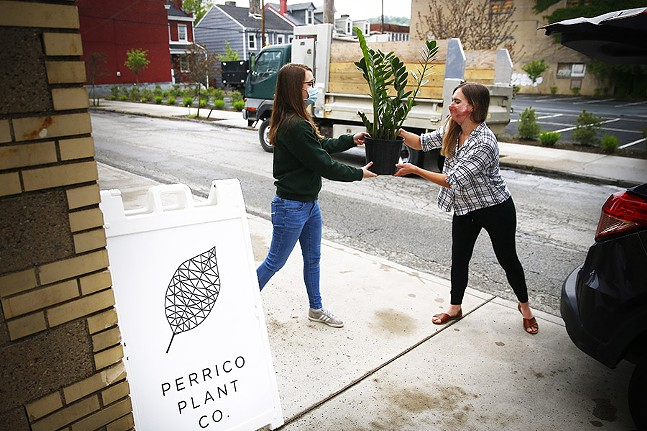 Abi Falcioni, owner of Perrico Plant Co., hands off a plant to customer Kelly Glover for a curbside pickup in Lawrenceville on Fri., May 22, 2020. - CP PHOTO: JARED WICKERHAM
