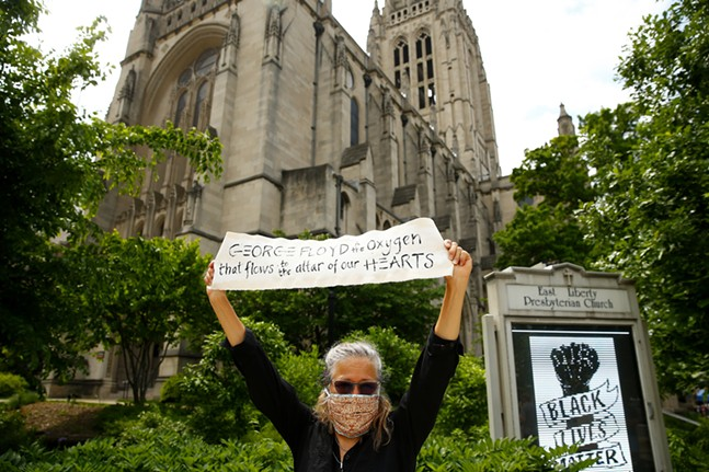 Catherine Parrish protests in front of East Liberty Presbyterian Church. - CP PHOTO: JARED WICKERHAM