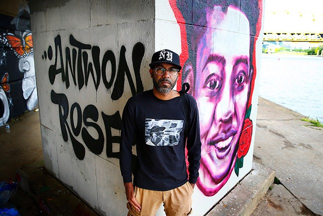 Pittsburgh Post-Gazette staff photographer Michael Santiago poses for a portrait in front of a Black Lives Matter mural with Antwon Rose painted behind him in Downtown Pittsburgh, along the Allegheny River, on Mon., June 15, 2020. - CP PHOTO: JARED WICKERHAM