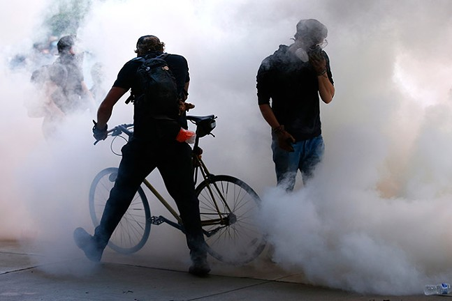 Protesters take cover from tear gas following a peaceful demonstration for George Floyd and Breonna Taylor in East Liberty on Mon., June 1, 2020. - CP PHOTO: JARED WICKERHAM