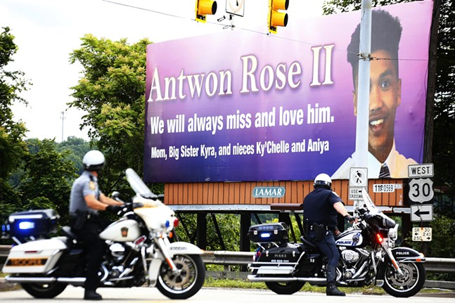 Pennsylvania State Police and North Versailles Police sit in front of the Antwon Rose II billboard. - CP PHOTO: JARED WICKERHAM
