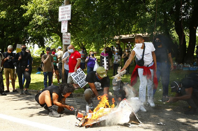 Marchers light the pinatas on fire after smashing them in Mellon Park. - CP PHOTO: JARED WICKERHAM