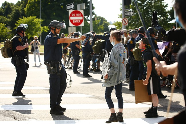 A Pittsburgh Police officer in riot gear holds up a canister of pepper spray to a protester as they take part in a Civil Saturdays protest that started in Market Square and marched through Downtown before being met by Pittsburgh Police in riot gear near the Fort Pitt Bridge on-ramp on Fri., July 4, 2020. - CP PHOTO: JARED WICKERHAM