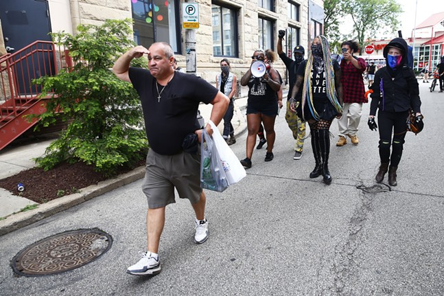 Organizers chase a man away from their group who was yelling racist remarks as he salutes the Pittsburgh police officer at the end of the street. - CP PHOTO: JARED WICKERHAM