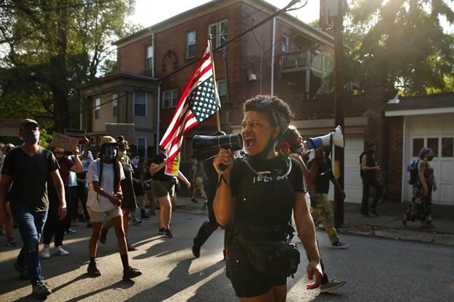 Jalina McClarin leads chants through the East Liberty neighborhood. - CP PHOTO: JARED WICKERHAM