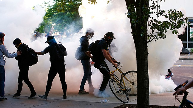 Protesters among tear gas fired by Pittsburgh Police on Centre Avenue during a march in the East Liberty on June 1 - CP PHOTO: JARED WICKERHAM
