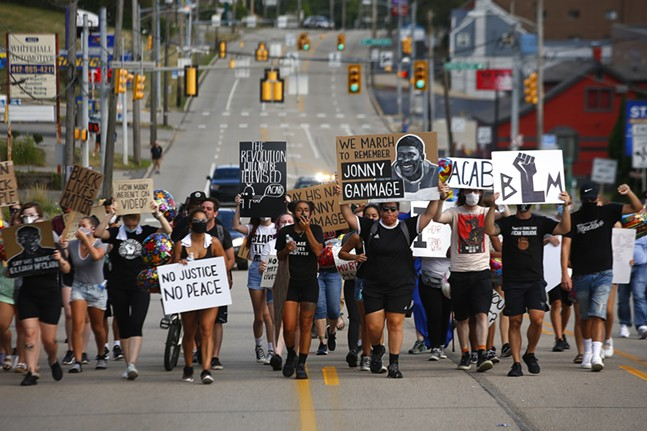 Protest organizer, Camille Redman, leads the group as they march through Brentwood from the Giant Eagle along Route 51 in honor of Jonny Gammage on his birthday. - CP PHOTO: JARED WICKERHAM