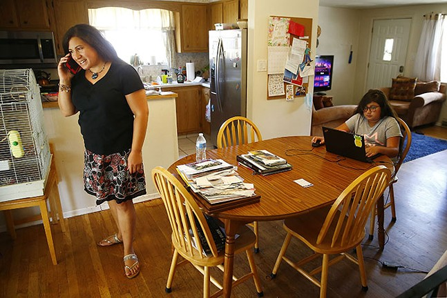María Manautou Matos takes a phone call while her daughter Gabriella, 11, plays on the computer in their home in Allison Park. - CP PHOTO: JARED WICKERHAM