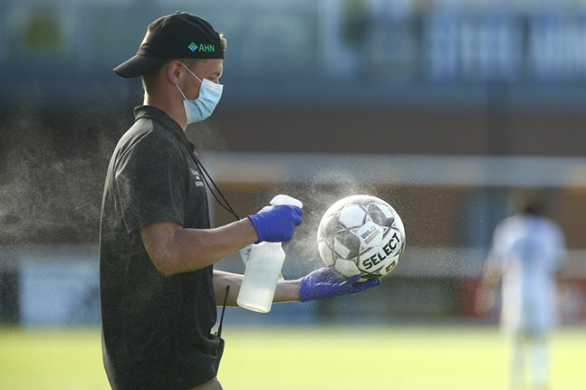 A Pittsburgh Riverhounds staff member disinfects a game ball in the first half. - CP PHOTO: JARED WICKERHAM