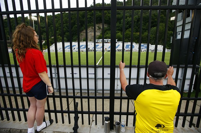 Fans at midfield watch the game through the fence along the Three Rivers Heritage Trail. - CP PHOTO: JARED WICKERHAM