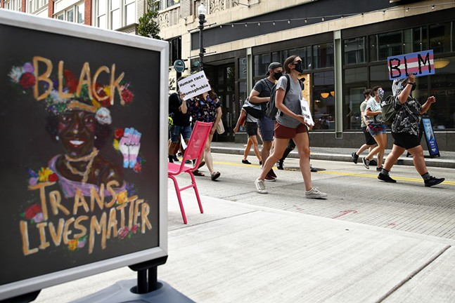 """A """"Black Trans Lives Matter"""" sign is seen as protesters walk by Millie's Ice Cream near Market Square. - CP PHOTO: JARED WICKERHAM"""