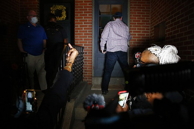 Pittsburgh Mayor Bill Peduto returns into his house after an exchange with protesters ends in an impasse. - CP PHOTO: JARED WICKERHAM