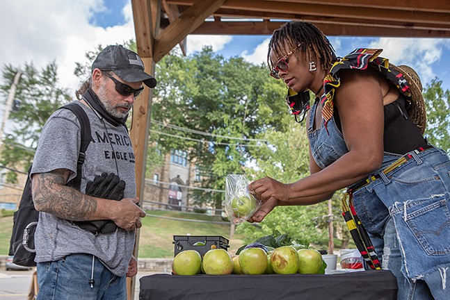 Ian Kriebel (left), an Army veteran and lover of fruit, purchased green apples from the weekly - farmers' market organized by Ebony Lunsford-Evans, owner of FarmerGirlEB in the West End. - PHOTO: BRIAN COOK